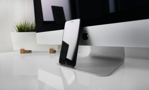 iphone leaning against and imac